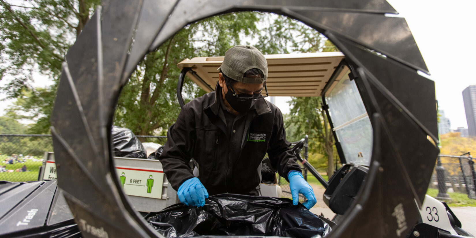 Staff member Danila Maturan photographed through the open lid of a trash can.