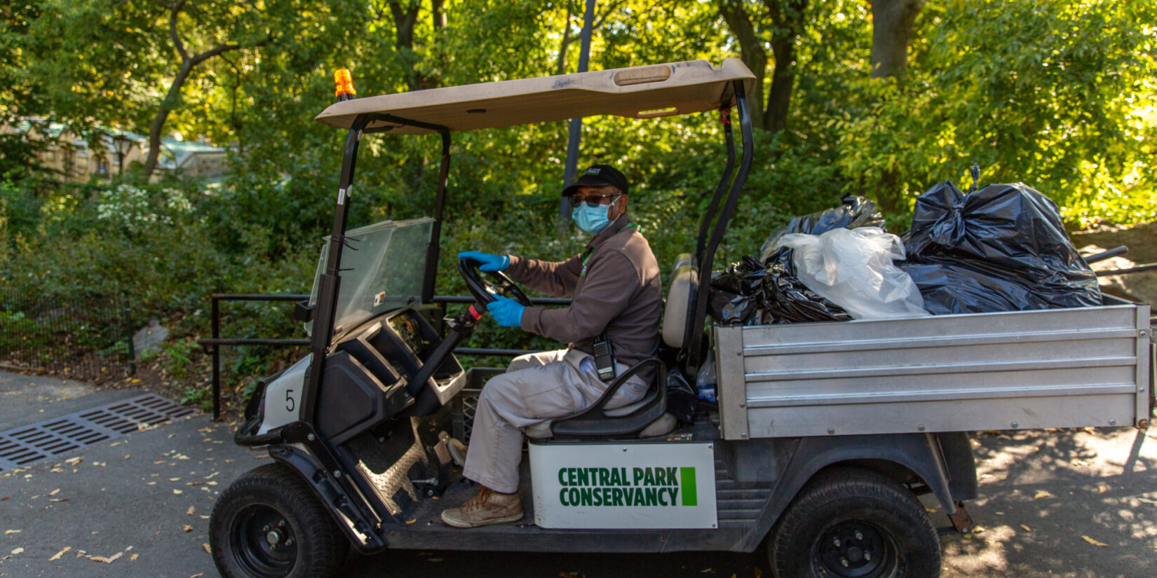 Staff member Rolly Tejada at the wheel of an electric cart used to haul small trash bags through Central Park.