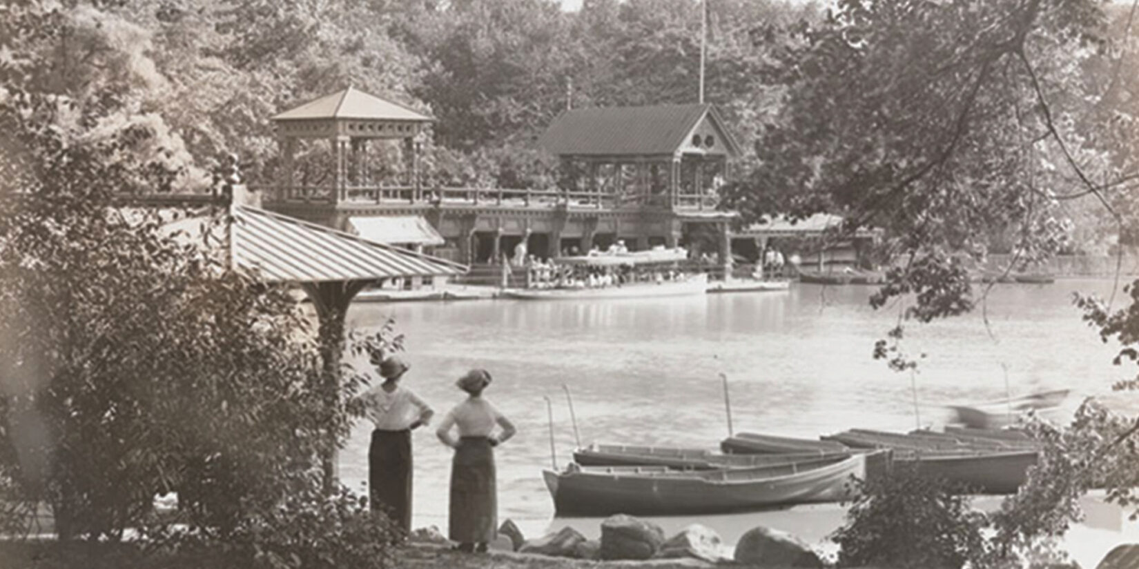 Contemporary photo showing 2 women on the shore of the Lake, with rustic structures in the foreground and background