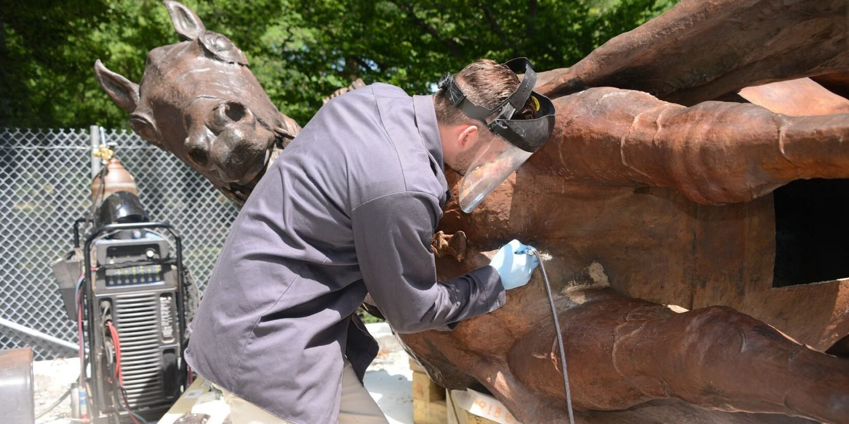 A welder works on the horse as the statue lays on one side.