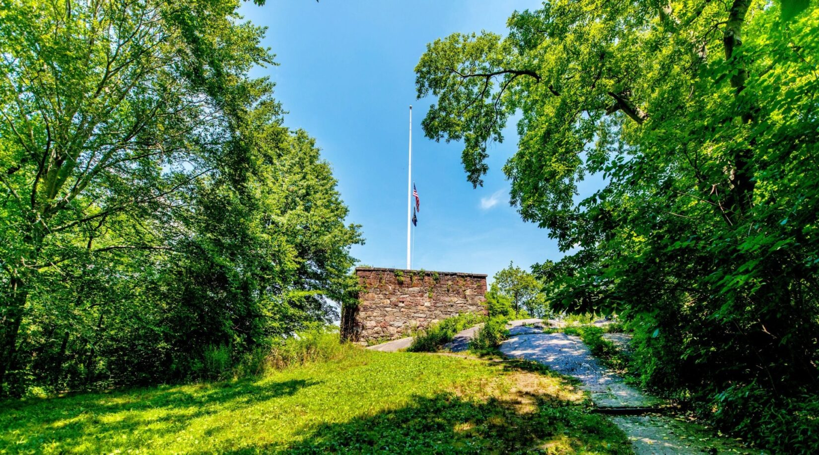 A view looking up the hill to the Blockhouse, topped with a white flagpole and a flag at half mast.