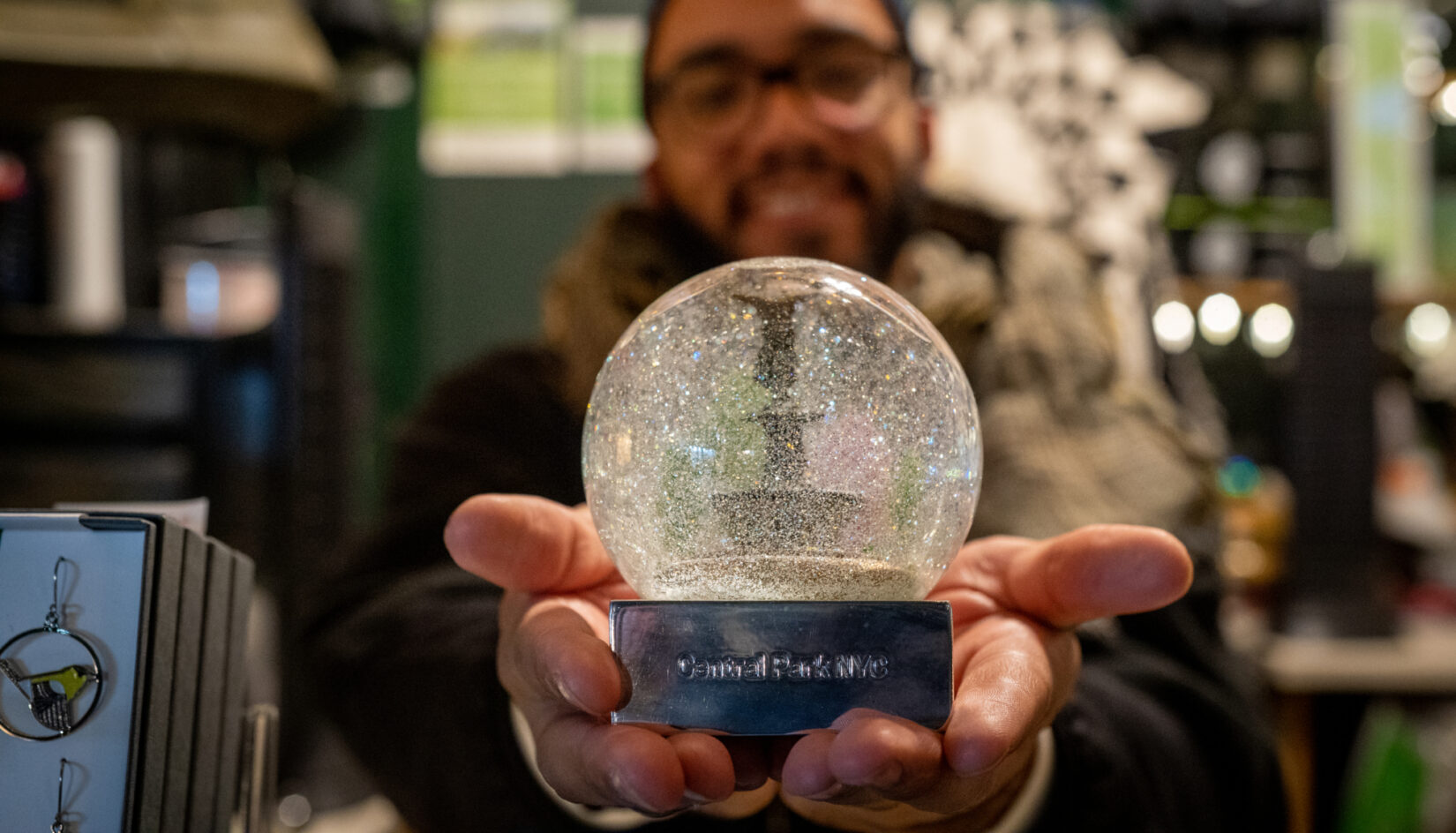 Close-up of hands holding a snow globe of Bethesda Fountain