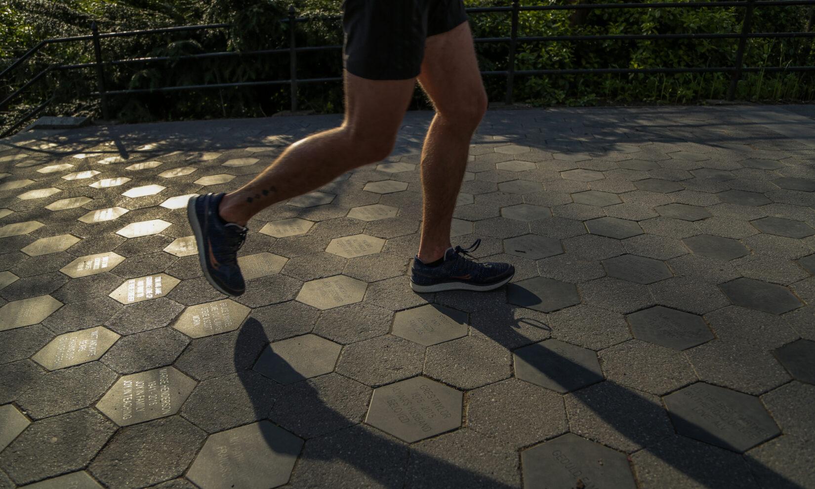 A runner jogs over the memorial stones of Gilder Run, shot in twilight