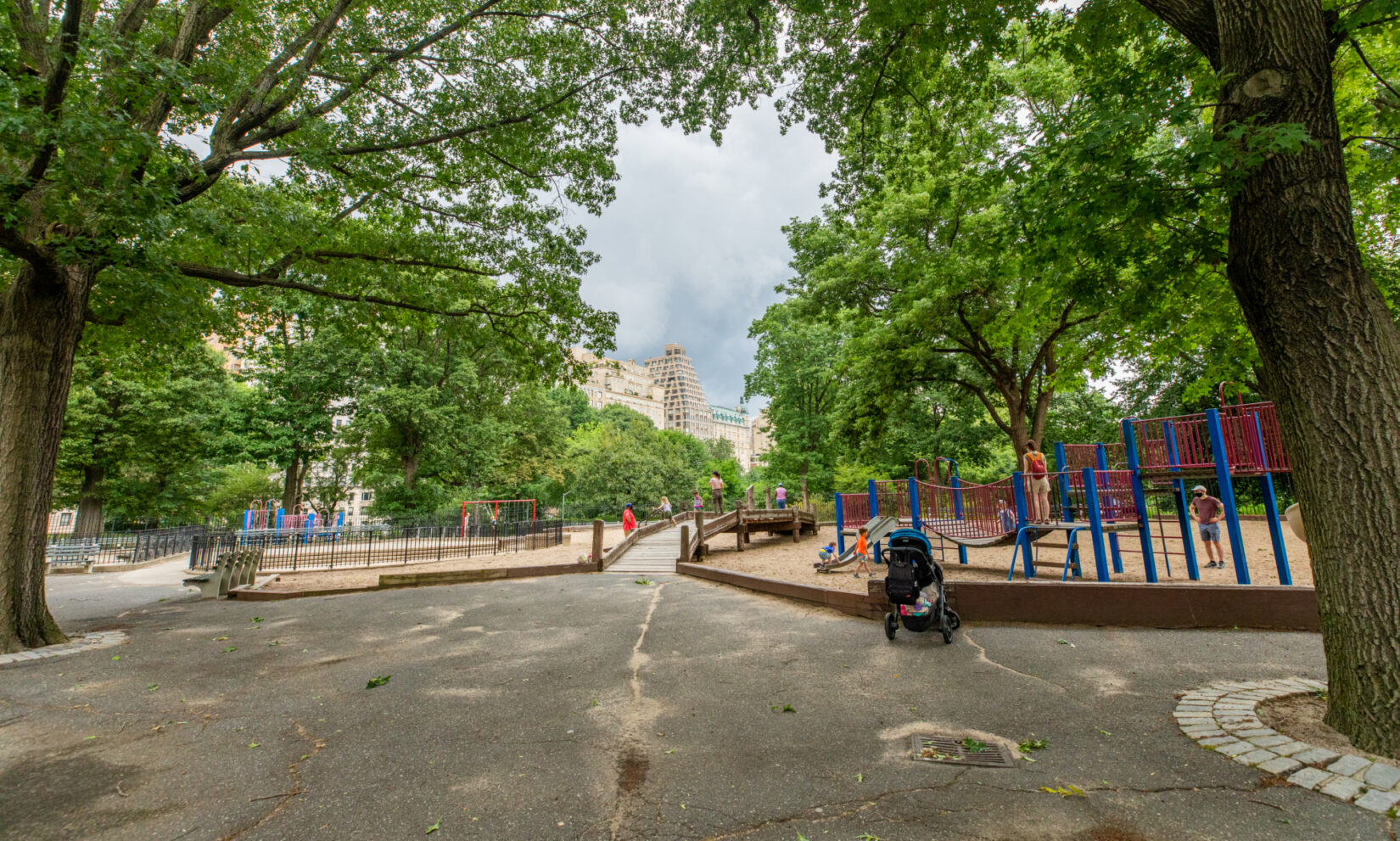 Looking down the Park path and across the rustic footbridge of the playground in summer.