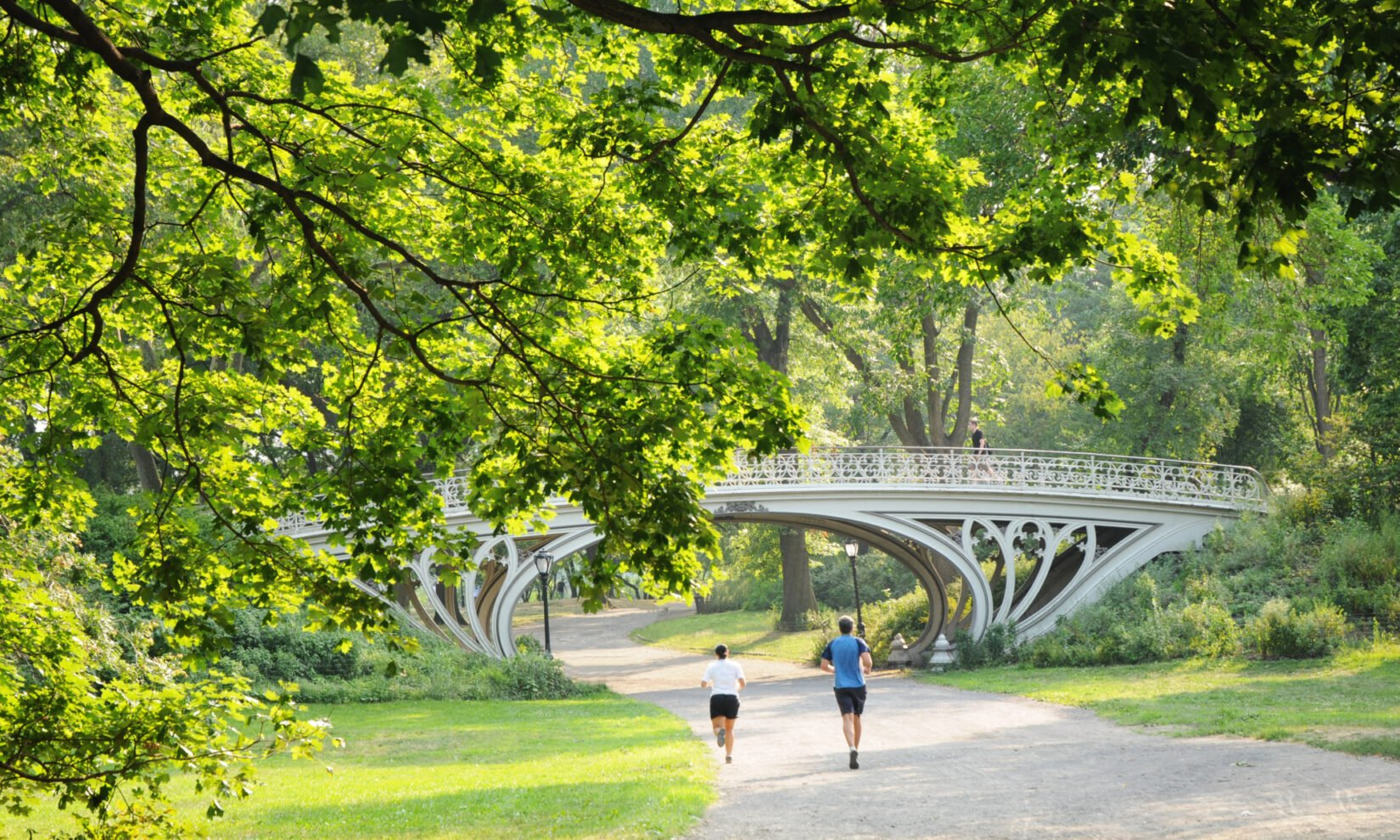 A pair of joggers on the bridle path head under Bridge 28 and a canopy of spring-green trees.