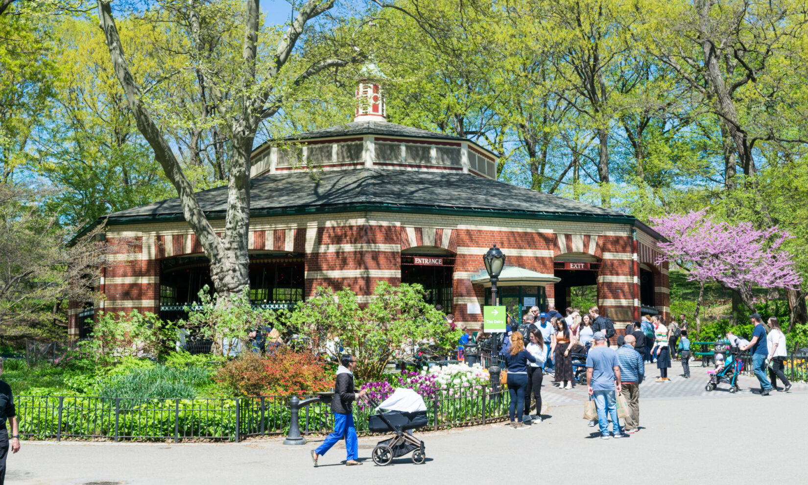Families with toddlers and strollers crowd the plaza in front of the carousel on a clear spring day