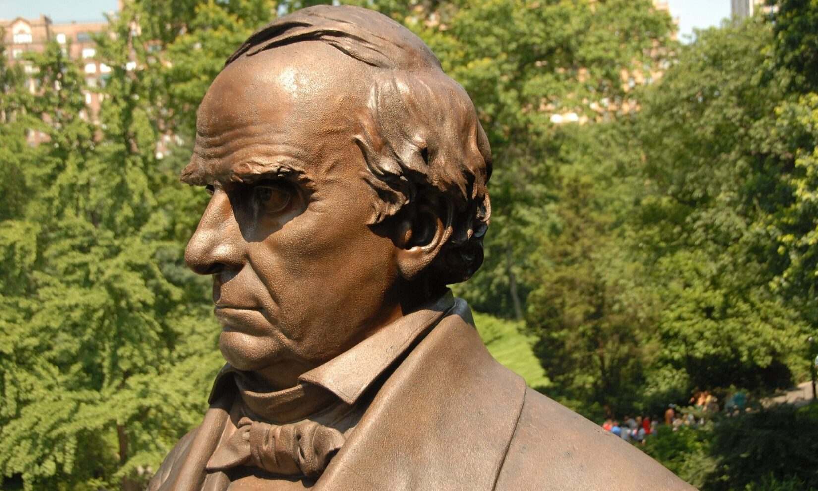 A closer view of Webster's profile against a blue sky and greenery.