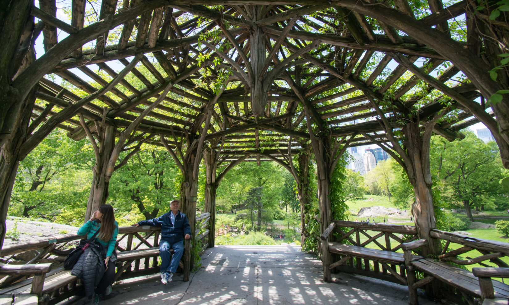 Two park-goers relax on benches under the timbers of the rustic summerhouse