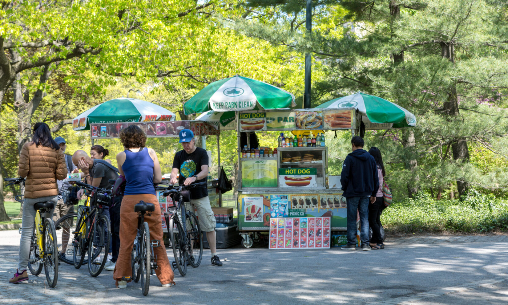 A typical Park food vendor, selling hot dogs, ice cream treats, and beverages under green and white umbrellas.