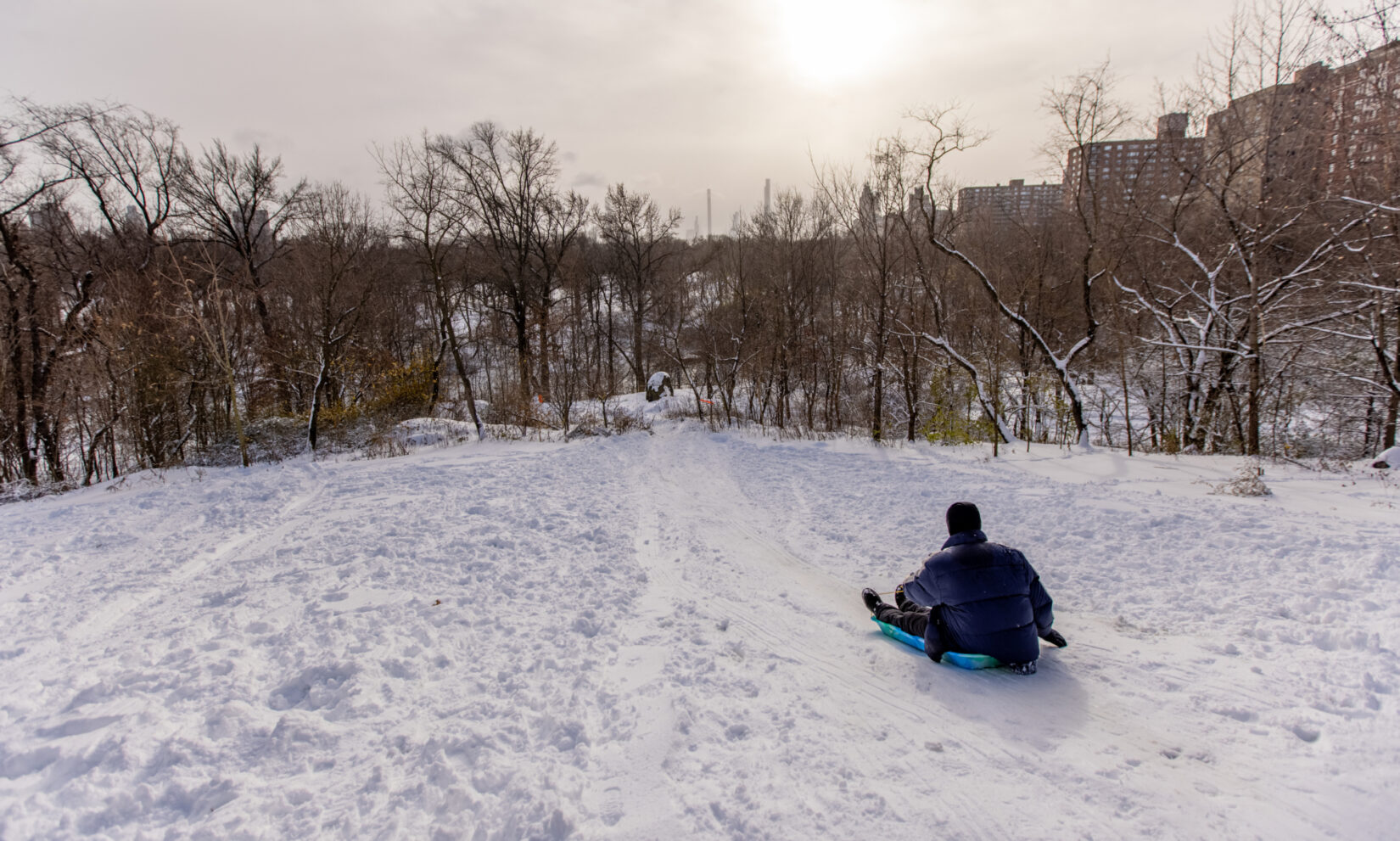 Looking down a snowy slope as a lone sled rider heads for the bottom