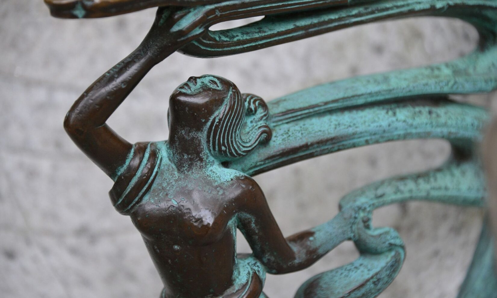 Sculptural detail of the bench shows a woman form, reaching up.