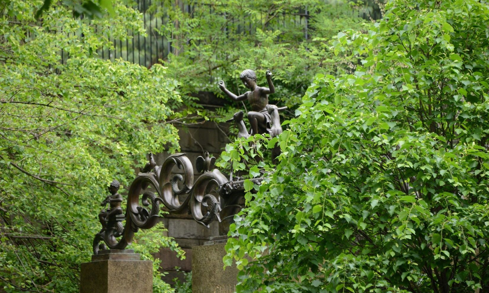 The figures at the top of the gate shown half-hidden in the neighboring tree canopy.