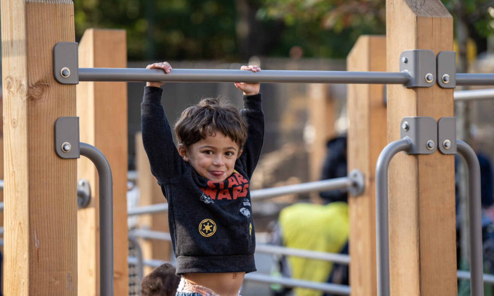A very young child hangs from a bar on the climbing equipment of the playspace.