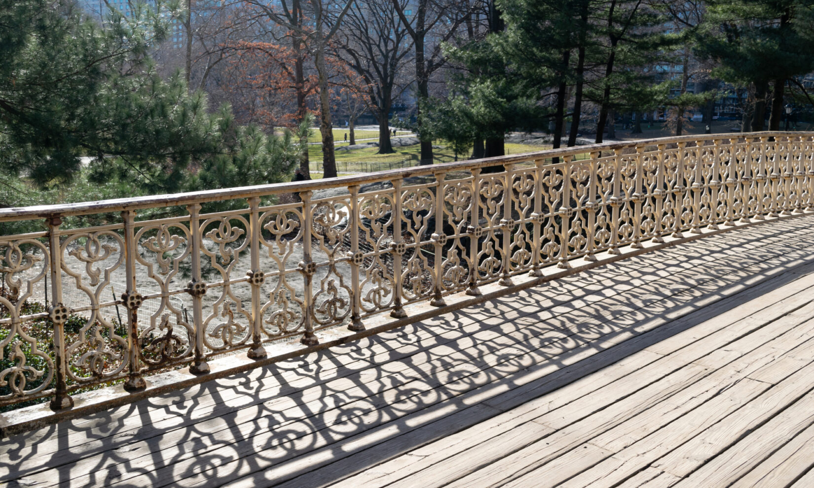 The intricate ironwork of the arch casts interesting shadows on  wooden planking.