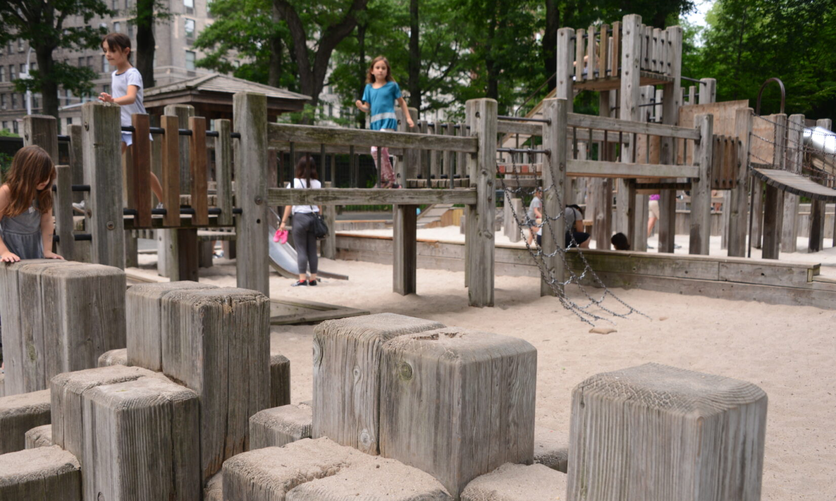 A girl crosses a wooden bridge spanning a sand pit in the playground.