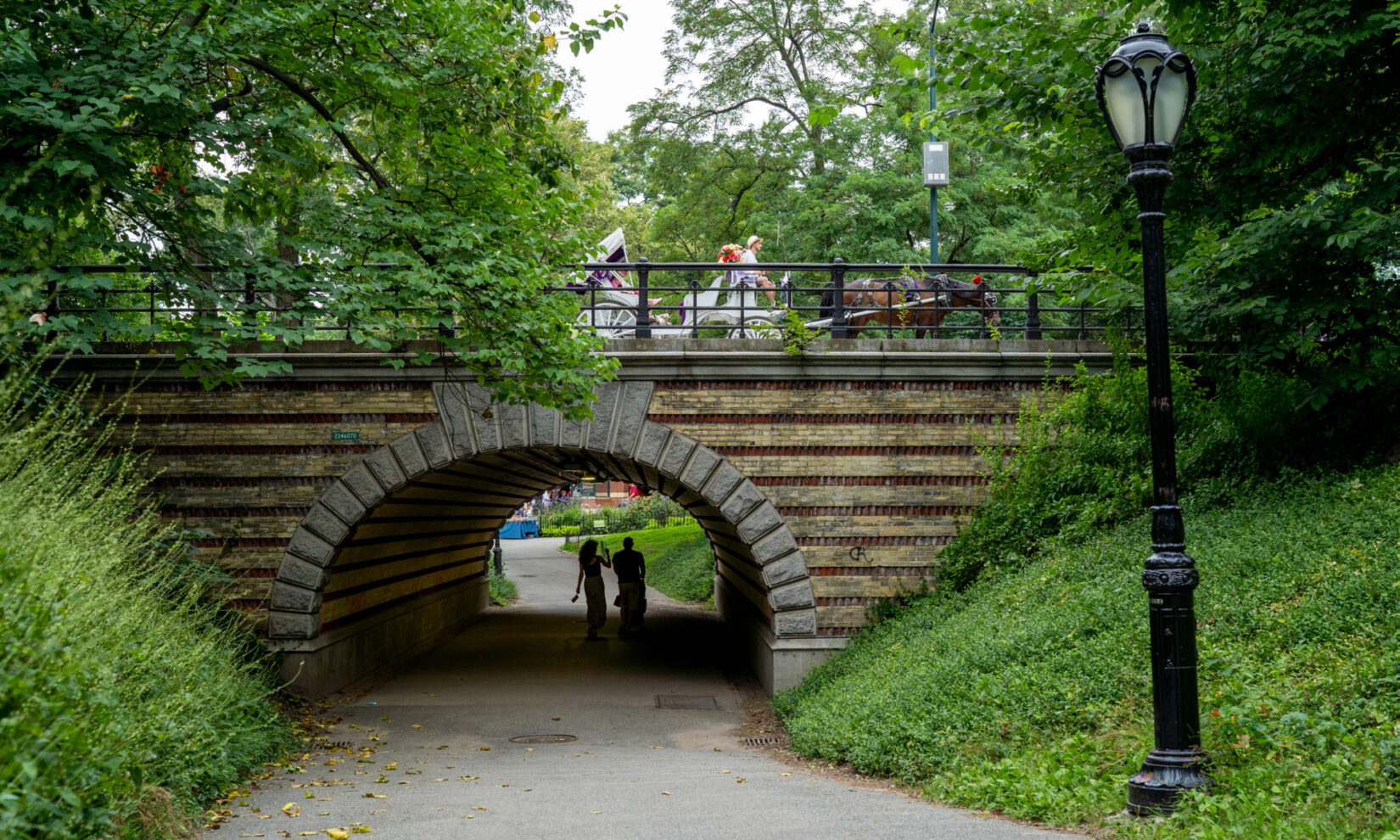 Strollers beneath the arch seem unaware of the horse and carriage on the drive above it.