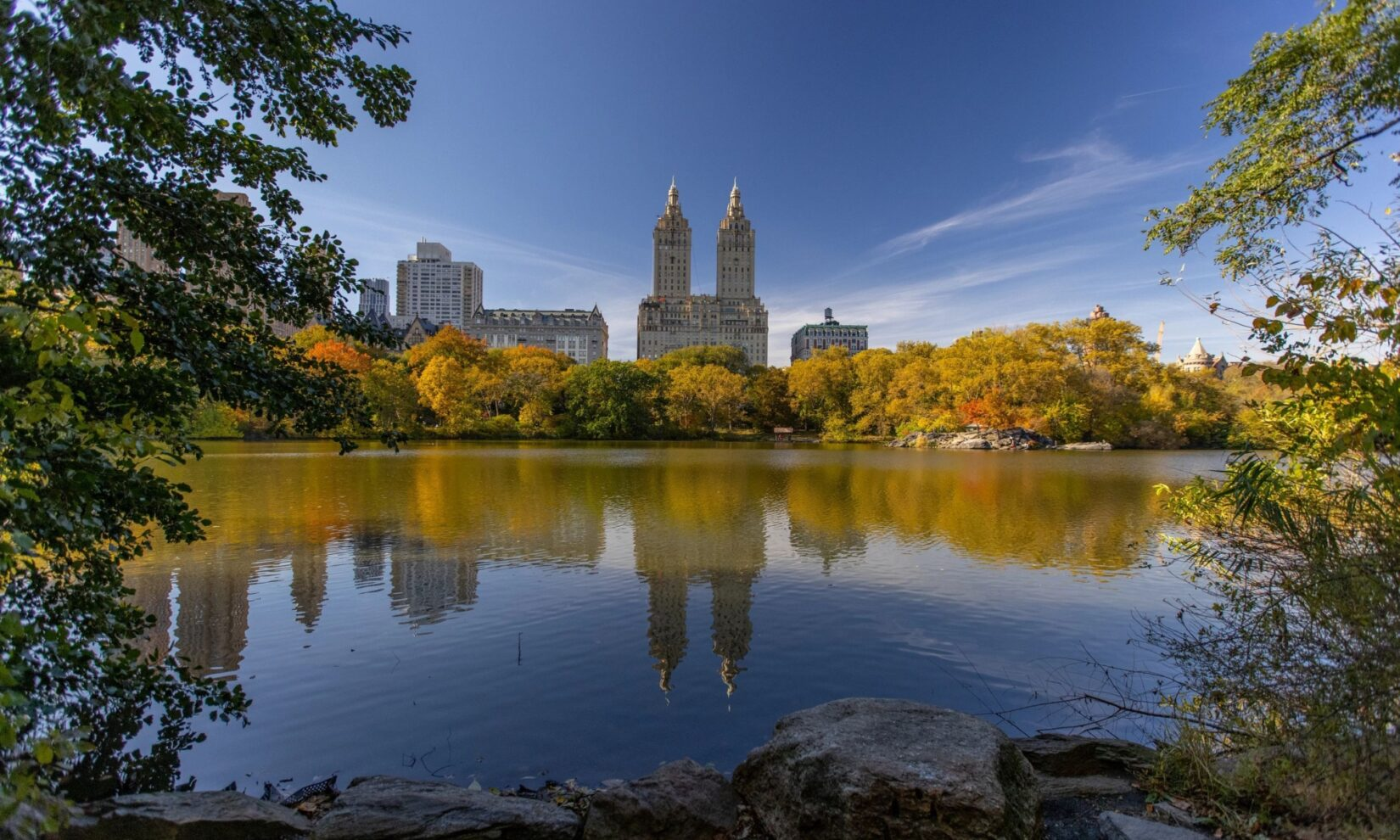 Buildings on Central Park West are reflected in still waters, viewed from the other side of the Lake in the Ramble.