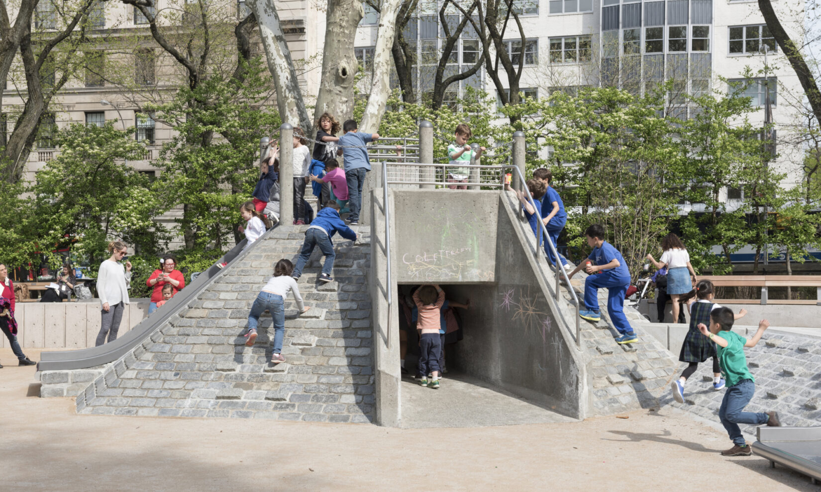 Kids clamber over, and walk under, the stone climbing apparatus in the playground.