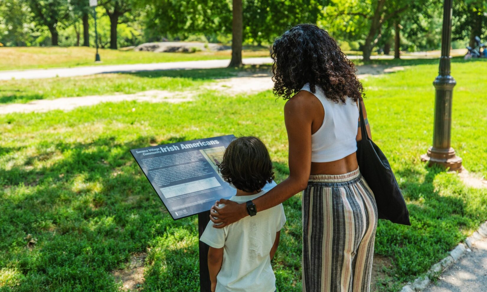 A woman and a child reading one of the in-Park signs describing Seneca Village