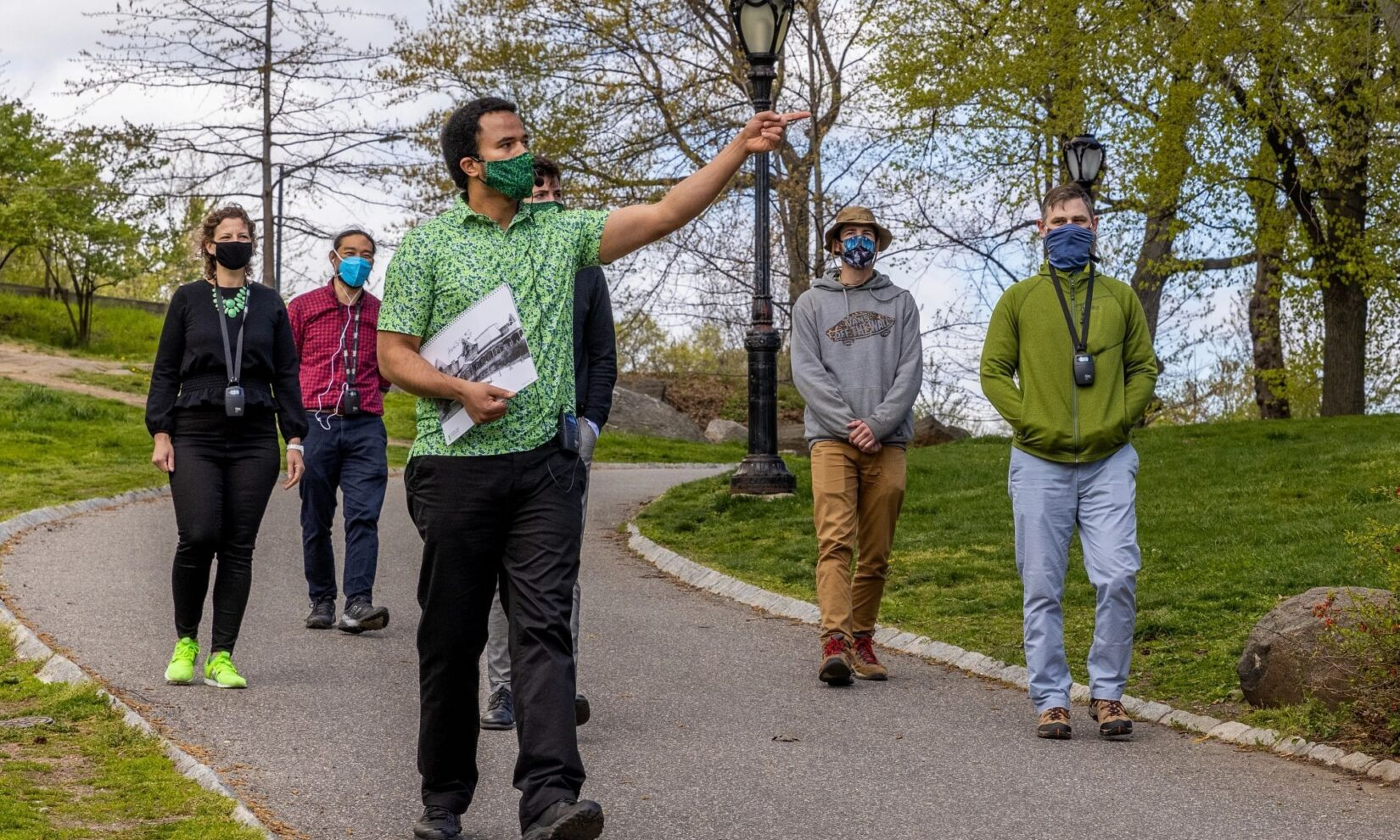A Conservancy staff member leads a small group on a tour dow a park path