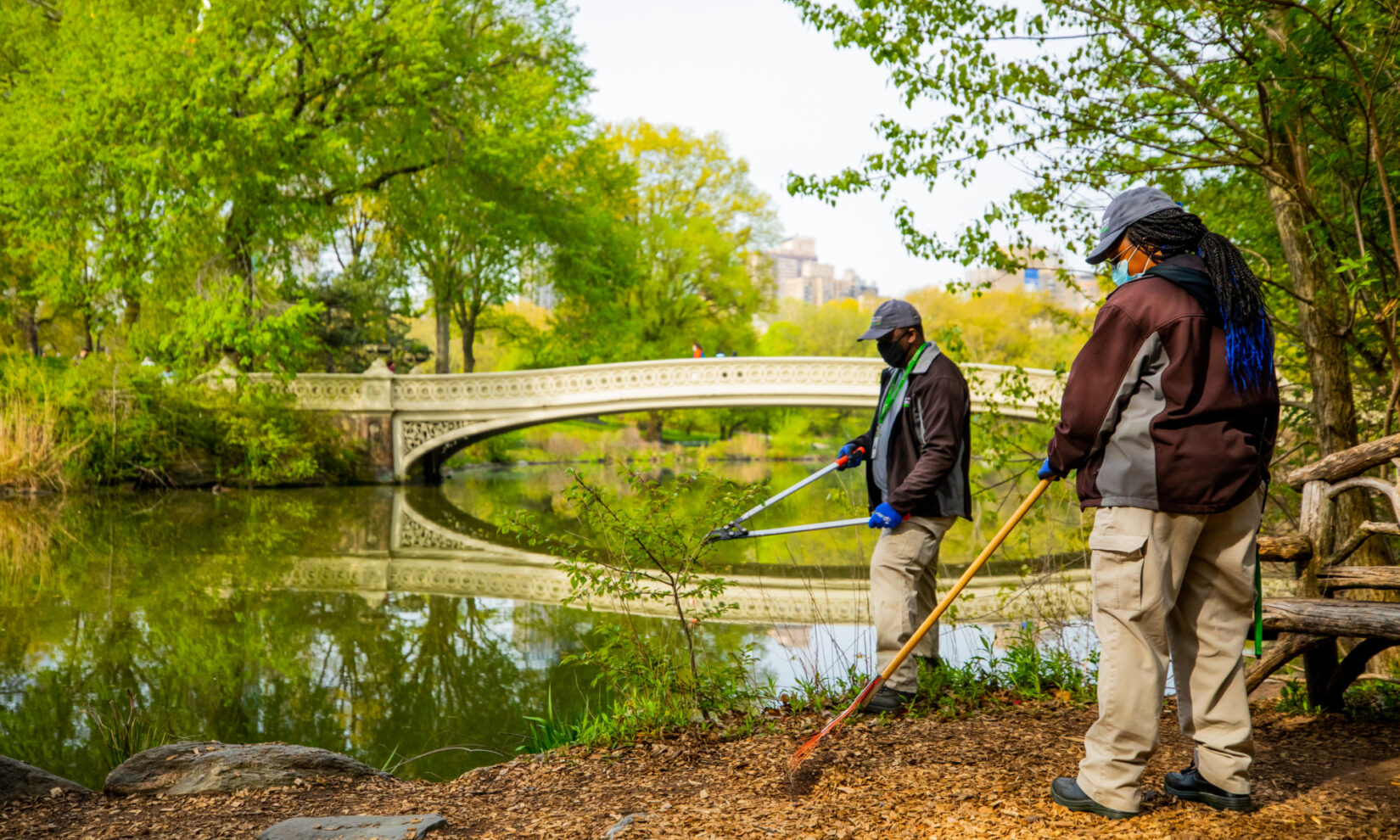 Two staff members tending to the embankment of the Lake with Bow Bridge in the background