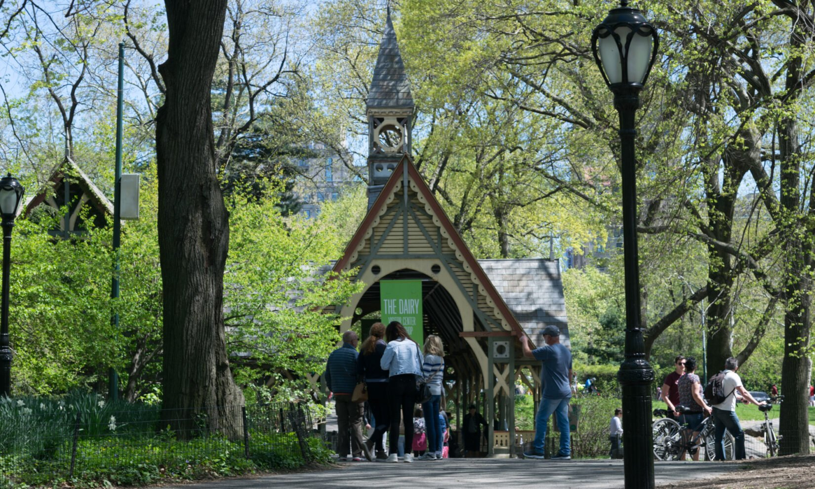 Park-goers congregate in dappled spring sunlight outside the Dairy