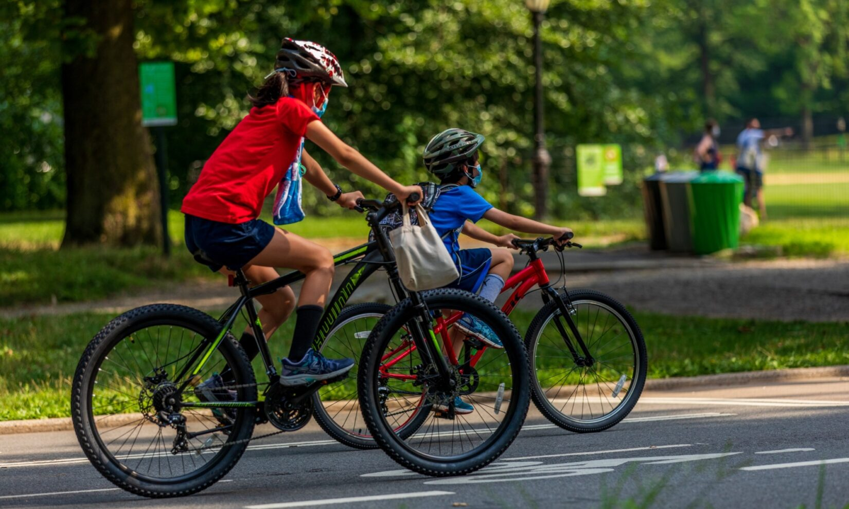 Two kids in helmets riding mountain bikes on a Park roadway