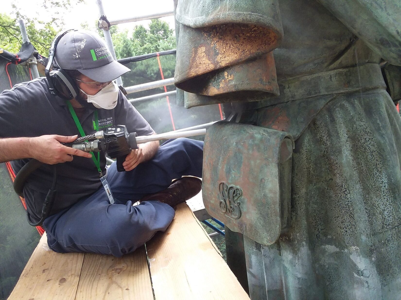 A worker power cleans the bronze statue.