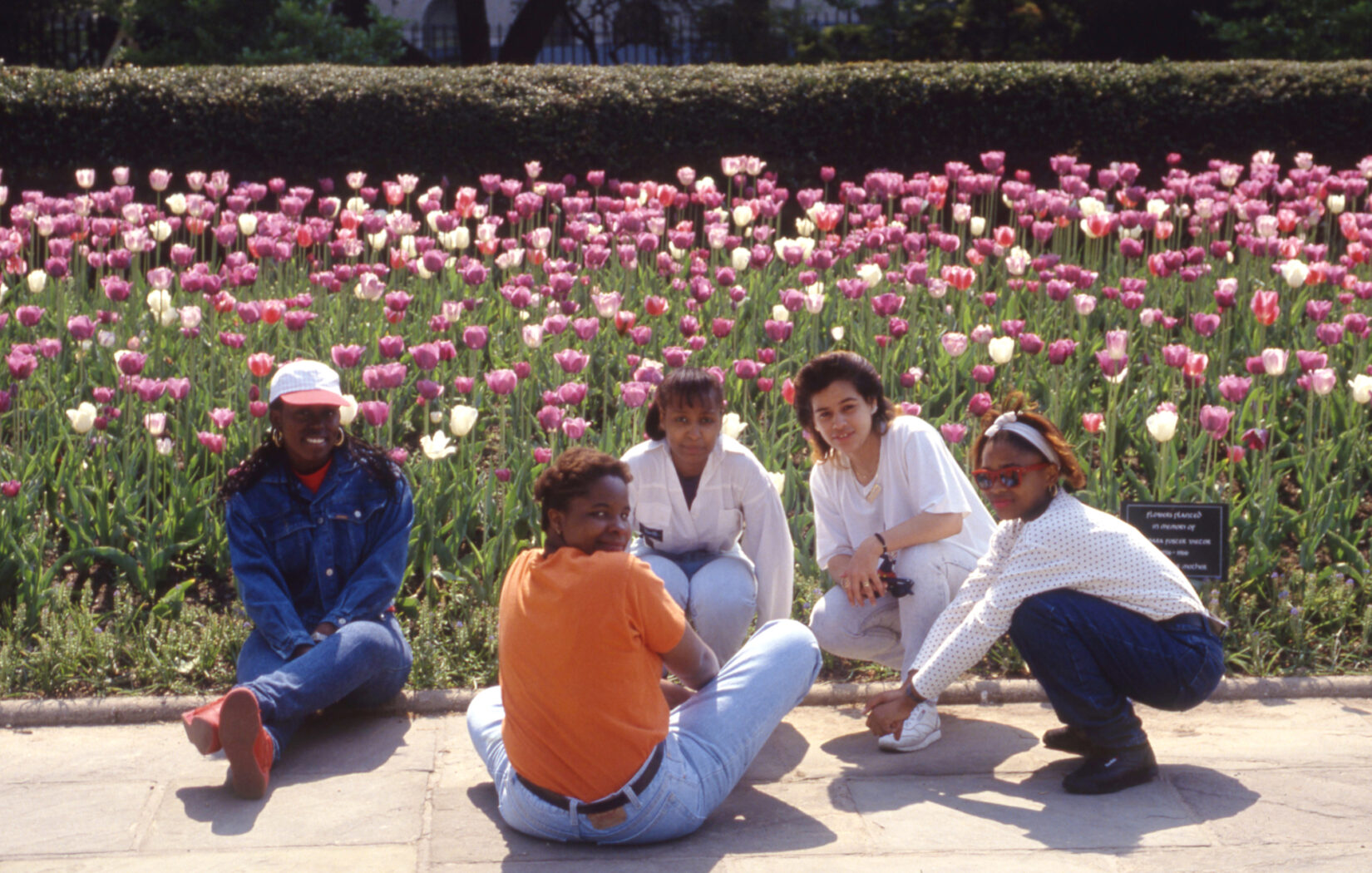Five young women crouching and sitting on a path in the Garden