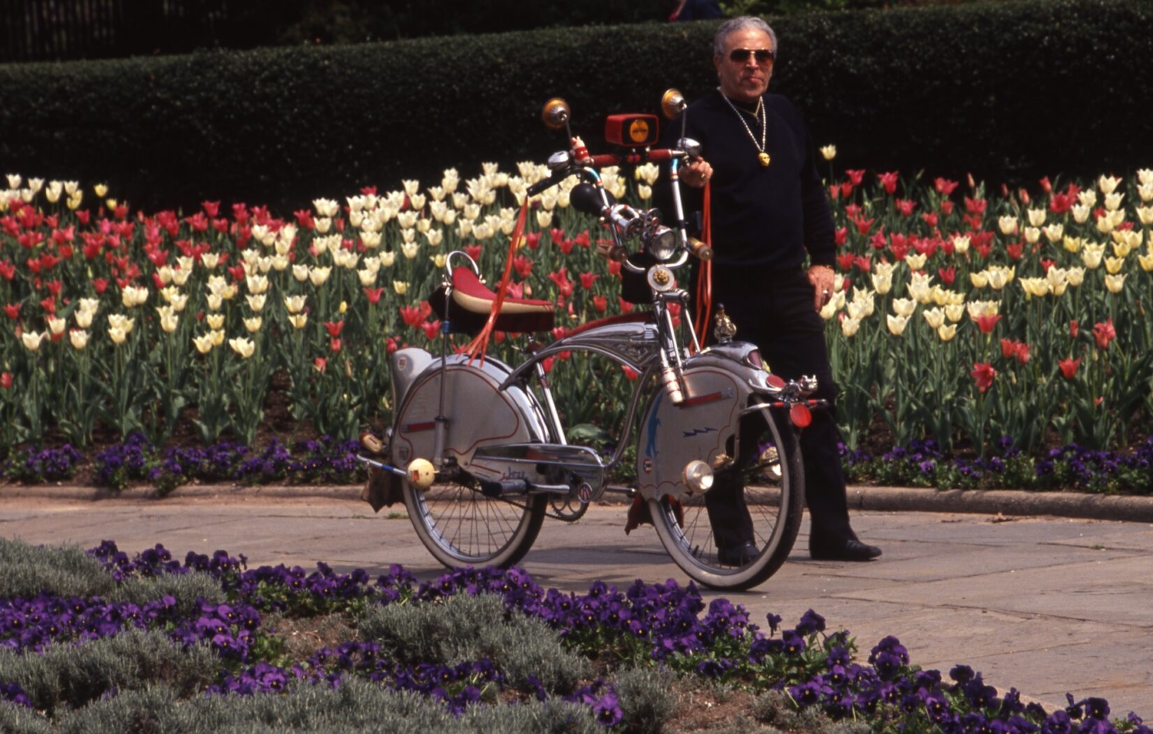 A man dressed in black walks his bicycle in the Garden. The bicycle is tricked out with a banana seat, high chrome handlebars accentuated with streamers, mirrors and an old-fashioned horn.