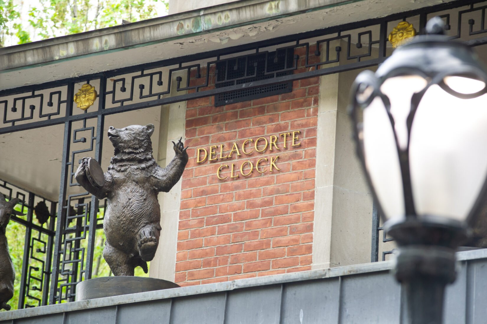A playful statue of a bear dances around the Delacorte Clock