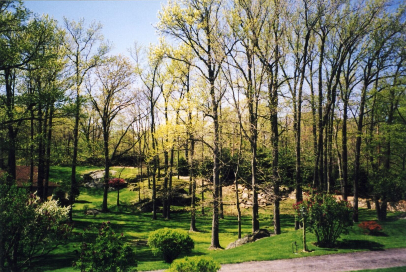 A well-tended landscape of lawn, outcroppings, and trees