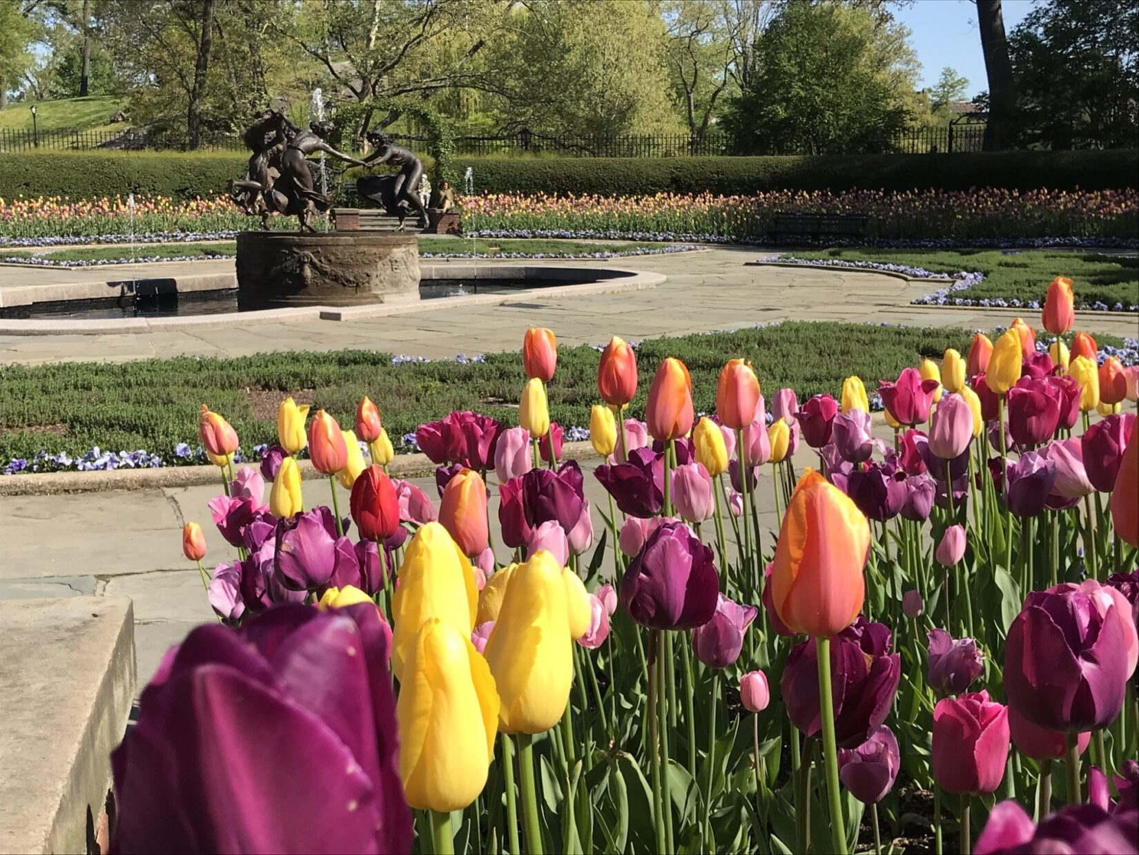 The fountain is pictured with yellow, pink, and purple flowers in the foreground.