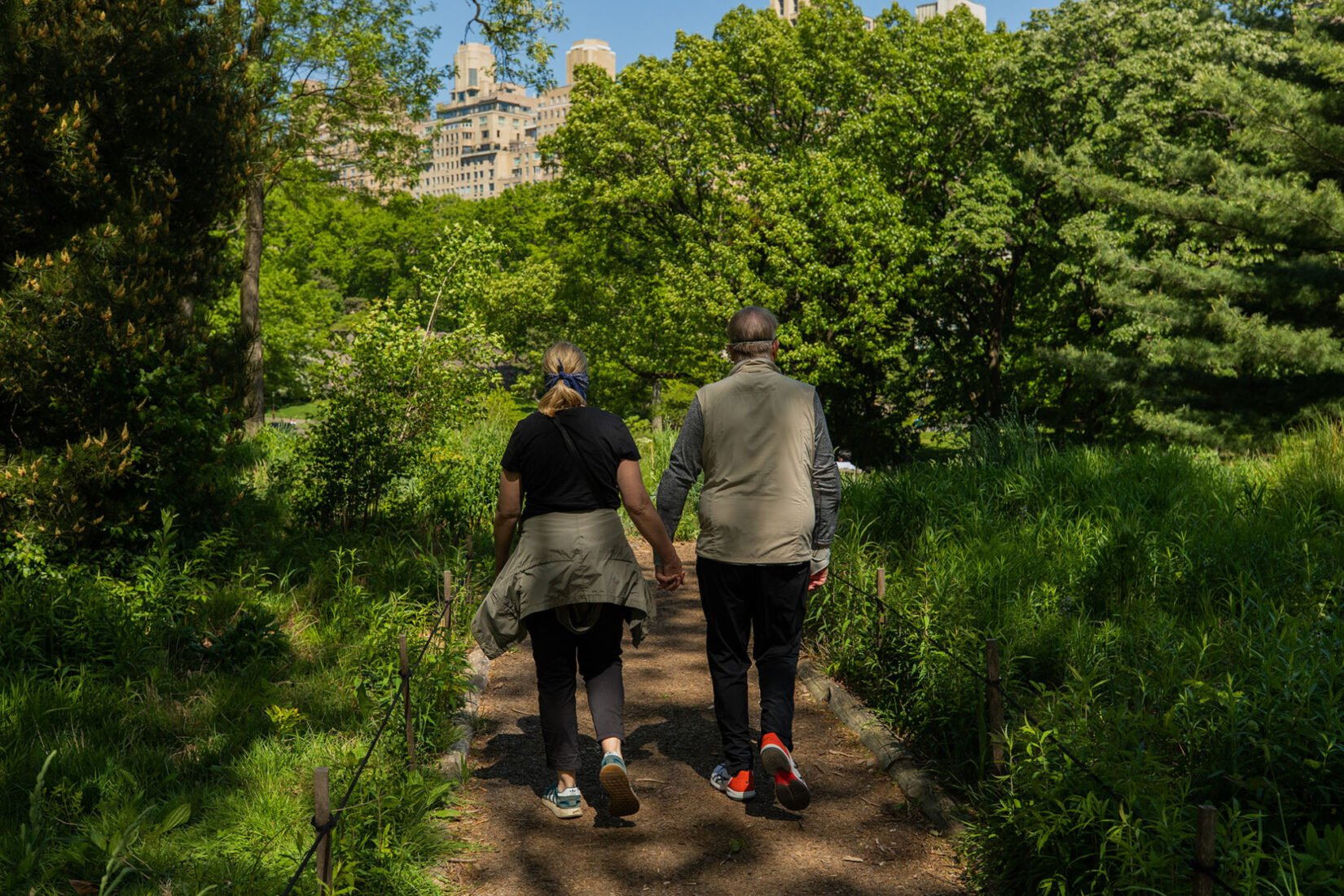 A couple walk hand-in-hand down a romantic, sunlit footpath