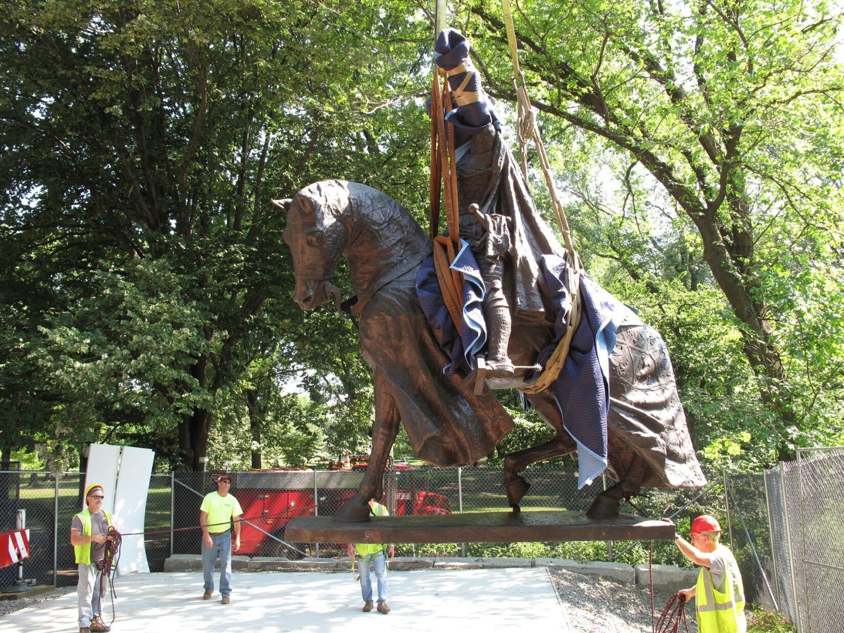 The statue is held in mid-air by a crane.