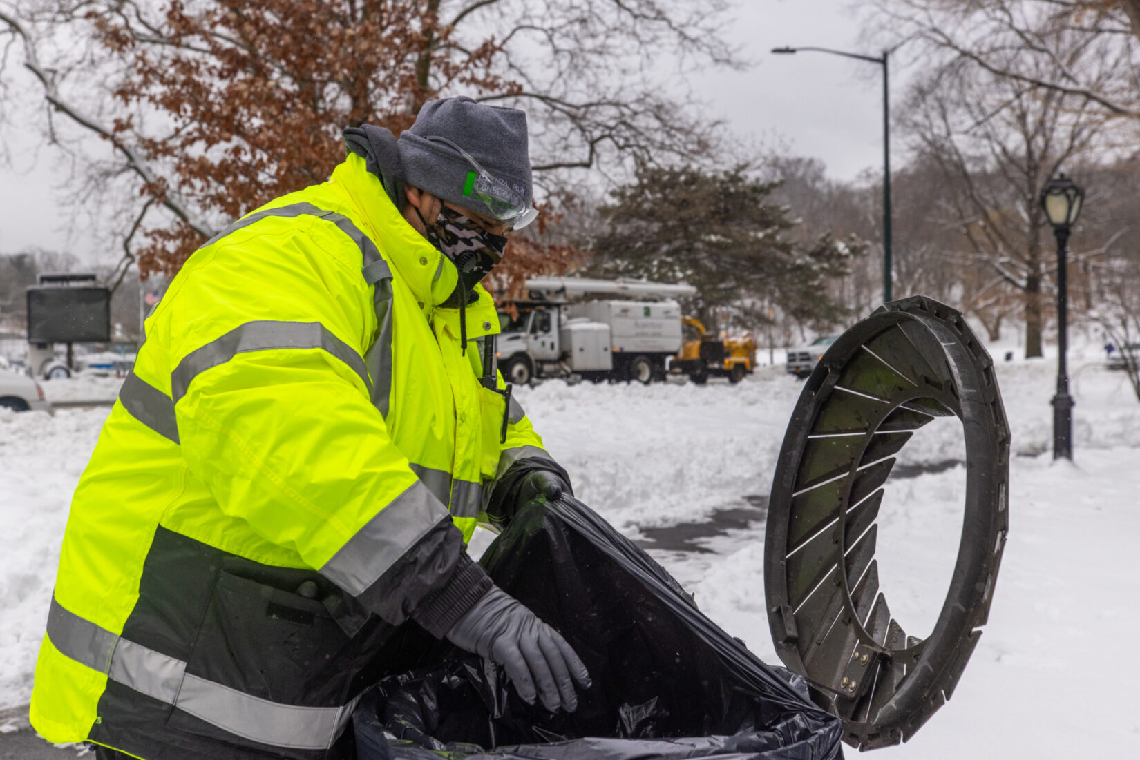 Staff member Raymond Acosta opens a trash can on a cold day in a snow-covered landscape.