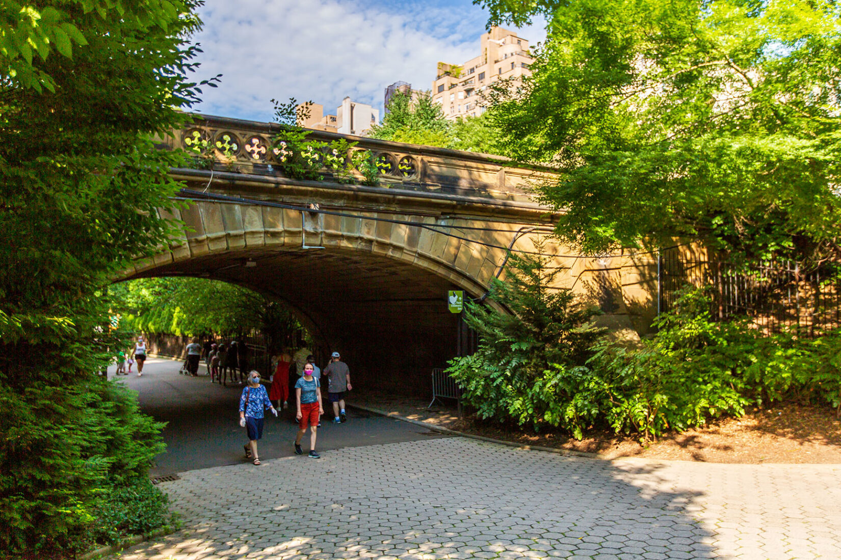 Masked parkgoers strolling under a bridge near the Children's Zoo in summer