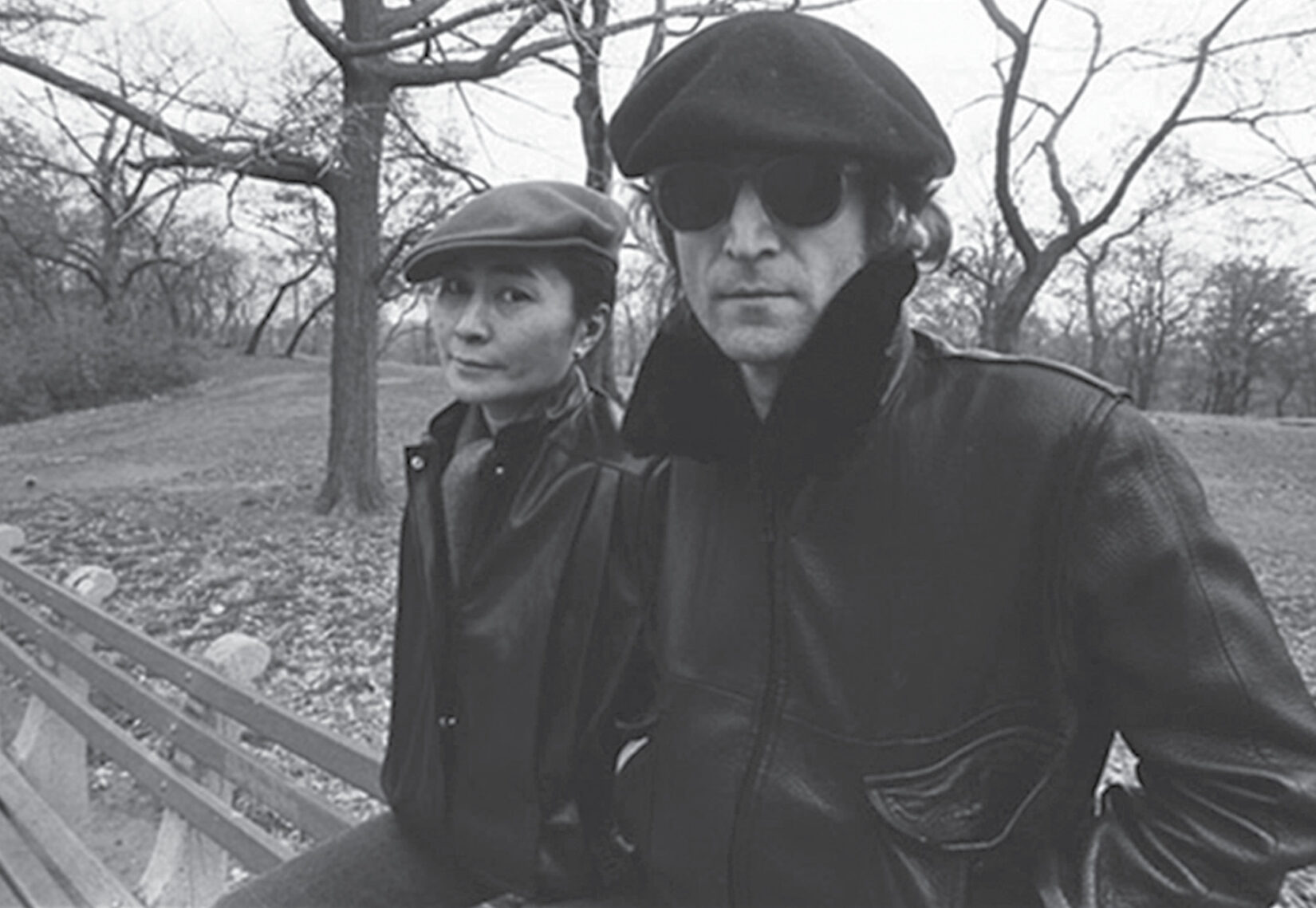 The couple are both wearing berets, sitting atop a park bench with leafless winter trees in the background.