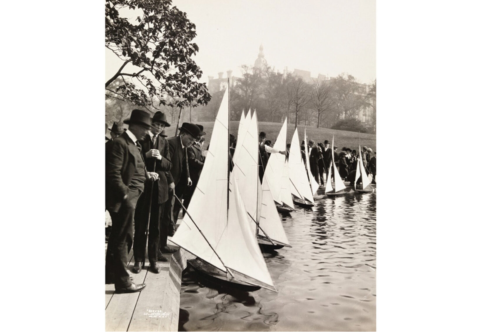 Black-and-white photo of men in suits tending model sailboats along the edge of Conservatory Water