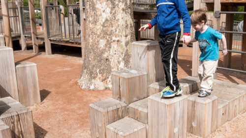 Kids balancing on wooden perches