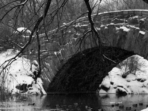 Black-and-white archival image of Gapstow Bridge in the snow