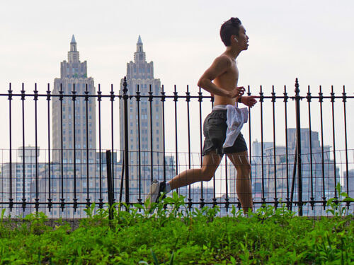 A shirtless runner silhouetted against the fencing of the reservoir