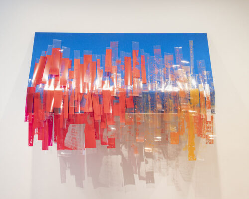 A sculptural piece photographed in a galler, featuring strips of red and transparent plastic drooping from a blue rectangle