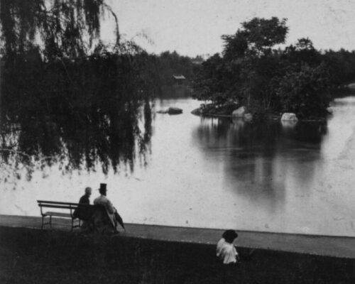 A photo from the late 19th century of Central Park showing a couple on a bench on the banks of a body of water.