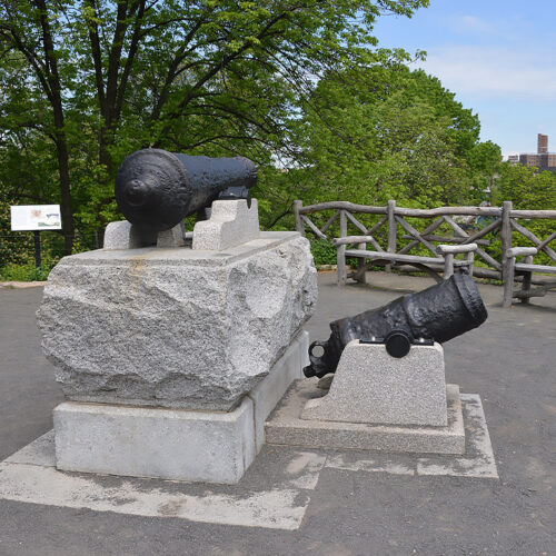 The cannon of Fort Clinton, surrounded by rustic seating and fences.