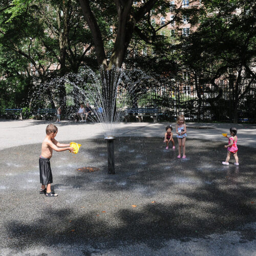 A boy plays at the water feature, before reconstruction
