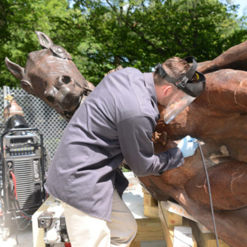 Workers restore the protective coating on the statue