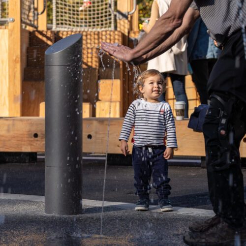 A toddler and parent at the water feature