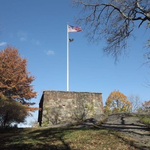 The American flag waves at the top of a pole mounted on the Blockhouse, against a clear blue sky.