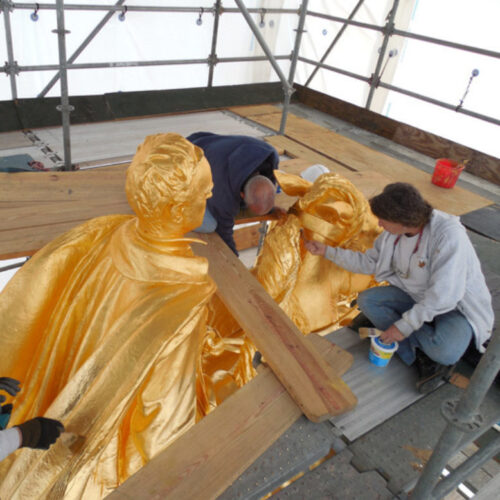 A worker on scaffolding restoring the Sherman statue